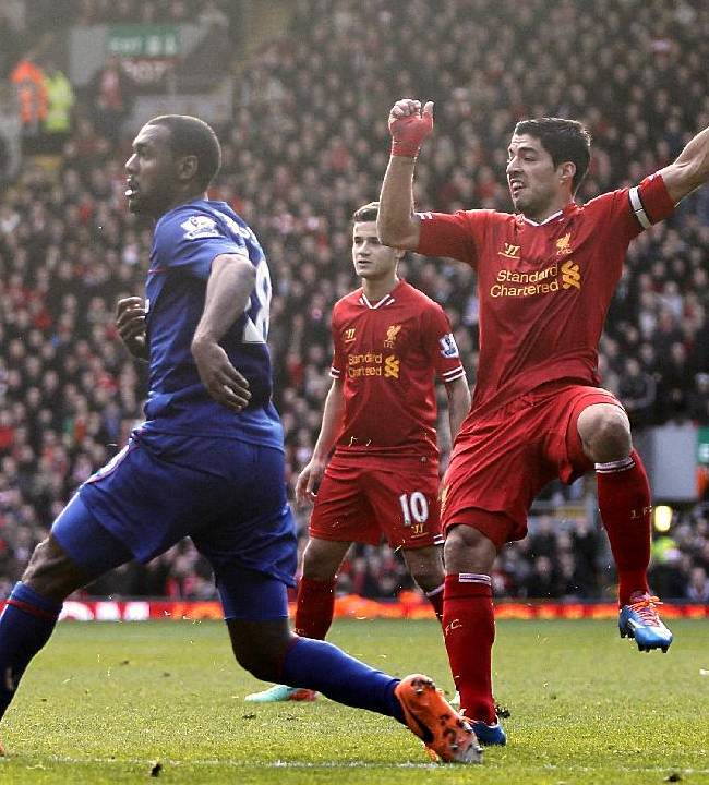 Liverpool's Luis Suarez, right, scores his team's third goal during their English Premier League soccer match against Cardiff City at Anfield, Liverpool, England, Saturday, Dec. 21, 2013