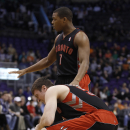 Toronto Raptors' Tyler Hansbrough, bottom, reacts as he is tended to by teammate Kyle Lowry (7) during the first half of an NBA basketball game against the Phoenix Suns, Friday, Dec. 6, 2013, in Phoenix The Associated Press