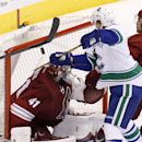 Vancouver Canucks' Zac Dalpe (21) uses a high stick to get to the puck as Phoenix Coyotes' Mike Smith (41) looks around for the puck during the third period of an NHL hockey game on Tuesday, March 4, 2014, in Glendale, Ariz. The Coyotes defeated the Canu