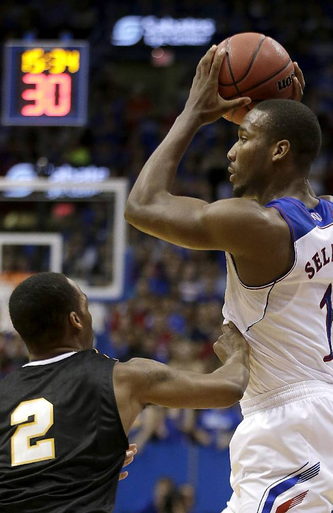 Kansas' Wayne Selden, Jr. (1) puts up a shot under pressure from Fort Hays State's James Fleming (2) during the first half of an exhibition NCAA college basketball game Tuesday, Nov. 5, 2013, in Lawrence, Kan