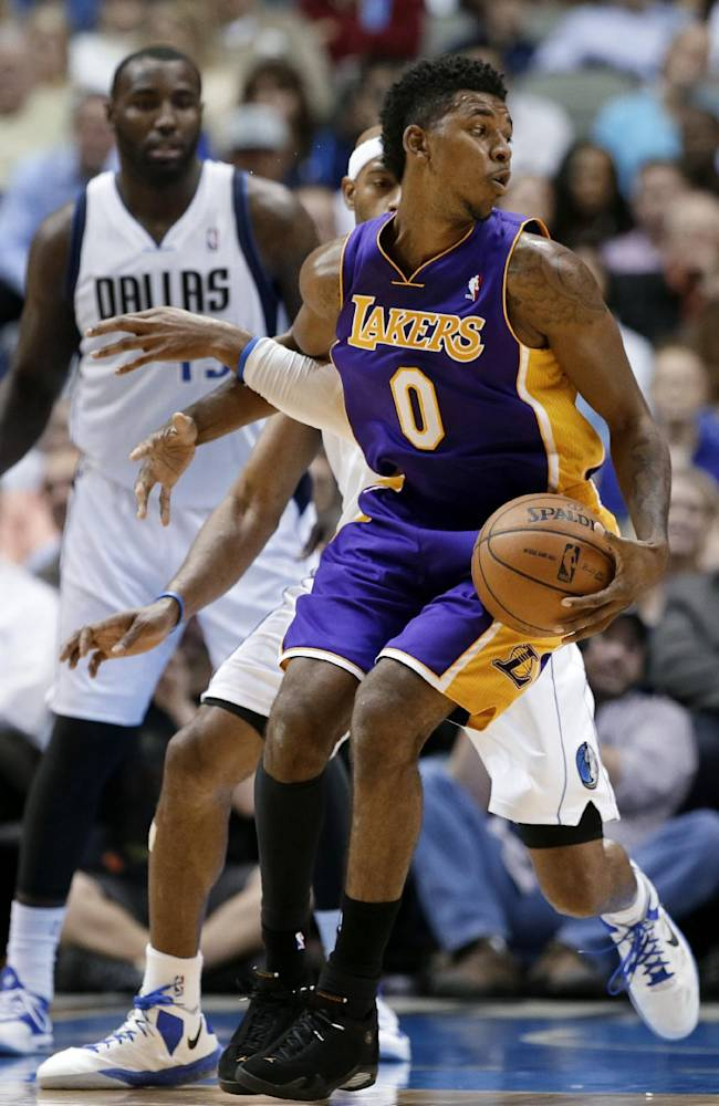 Los Angeles Lakers' Nick Young spins around to get by Dallas Mavericks' Vince Carter, center, during the second half of an NBA basketball game, Tuesday, Nov. 5, 2013, in Dallas. The Mavericks won 123-104