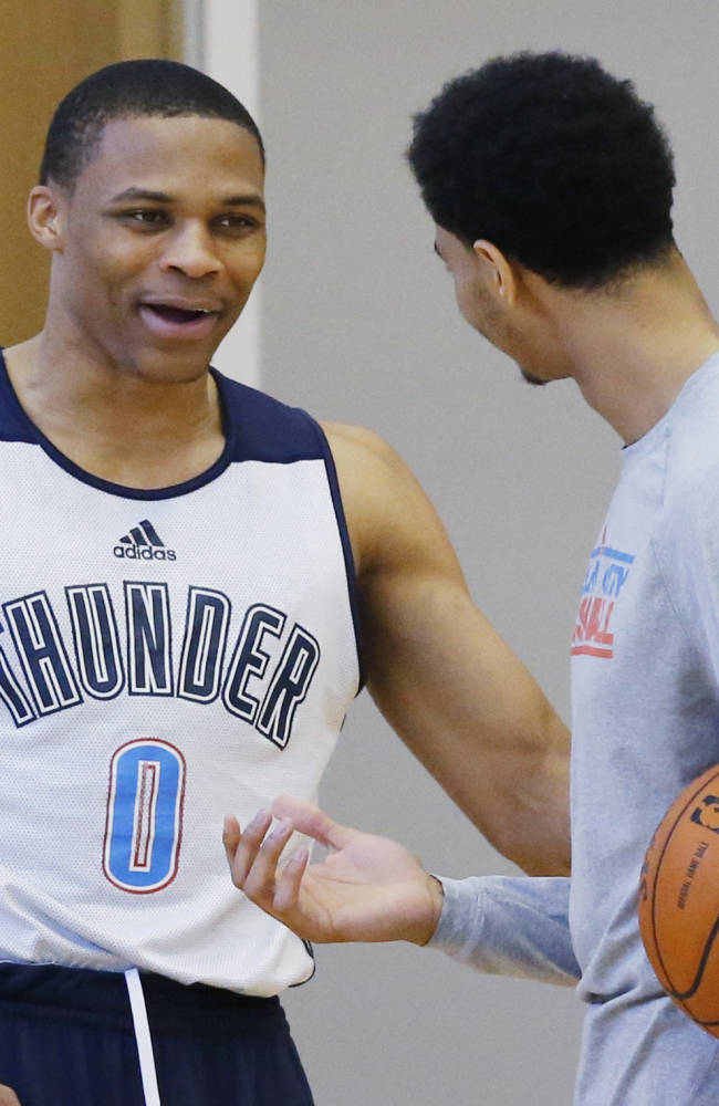 Oklahoma City Thunder guard Russell Westbrook (0) talks with teammate Jeremy Lamb following the NBA basketball team's practice in Oklahoma City, Friday, April 18, 2014. Oklahoma City will face the Memphis Grizzlies in the first round of the NBA playoffs
