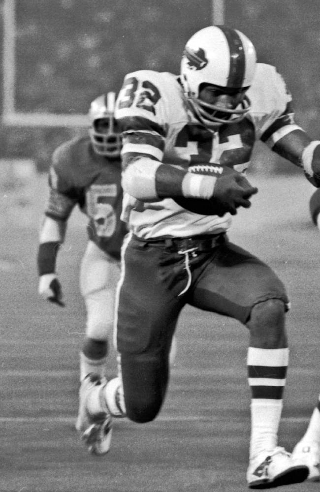 In this Nov. 25, 1976 file photo, Buffalo Bills' O.J. Simpson rushes through a large hole in the center fo the Detroit Lions defensive line to score on a 12-yard run for his second touchdown of the game in an NFL football game in Pontiac, Mich. Simpson added some