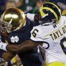 FILE - In this Sept. 22, 2012, file photo, Notre Dame's TJ Jones makes a catch against Michigan's Raymon Taylor during the first half of an NCAA college football game in South Bend, Ind. Nobody really knows how Notre Dame makes any of its decisions, though dropping a rivalry against the university that the Irish played their first football game ever against (Michigan) in 1887 would seem to be a mistake at first blush. (AP Photo/Darron Cummings, File)