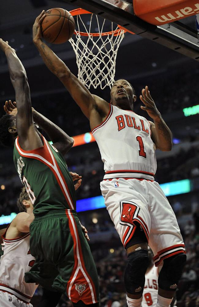 Chicago Bulls' Derrick Rose (1), goes up for a shot against Milwaukee Bucks' Larry Sanders (8), during the first half of an NBA preseason basketball game in Chicago, Monday, Oct. 21, 2013