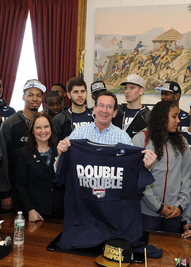 Connecticut Gov. Dannel P. Malloy holds a shirt in his office Sunday, April 13, 2014, in Hartford, Conn., as members of the UConn men's and women's basketball teams join him before a parade to honor their NCAA college basketball championships. AP Photo/Fred Beckham)