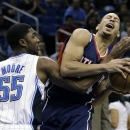 Atlanta Hawks' Devin Harris, right, draws a foul from Orlando Magic's E'Twaun Moore (55) while driving to the basket during the first half of an NBA basketball game, Wednesday, Feb. 13, 2013, in Orlando, Fla. (AP Photo/John Raoux)