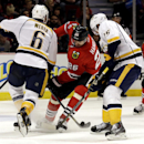 Chicago Blackhawks' Michal Handzus (26), center, battles for the puck against Nashville Predators' Shea Weber (6), left, and Craig Smith (15) during the second period of an NHL hockey game in Chicago, Sunday, March 23, 2014 The Associated Press
