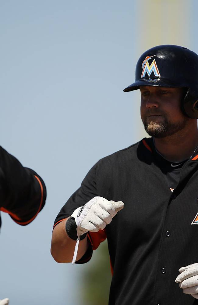 Miami Marlins' Casey McGehee, right, fist-bumps first base coach Perry Hill after hitting a single in the fourth inning of an exhibition spring training baseball game against the Detroit Tigers, Sunday, March 9, 2014, in Jupiter, Fla