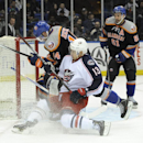 New York Islanders' Thomas Hickey (14) and Columbus Blue Jackets' Blake Comeau (14) collide in front of the net as Islanders' Frans Nielsen (51) defends from behind in the first period of an NHL hockey game on Sunday, March 23, 2014, in Uniondale, N.Y Th