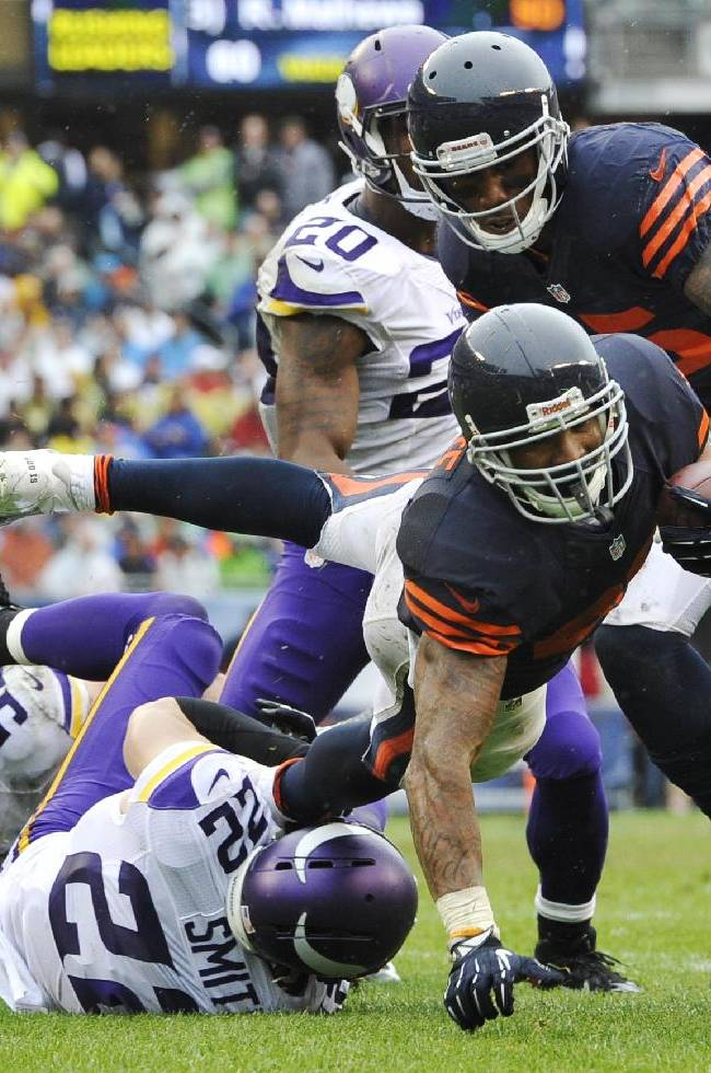Chicago Bears running back Matt Forte (22) dives to gain yardage as Minnesota Vikings safety Harrison Smith (22) tackles him during the second half of an NFL football game on Sunday, Sept. 15, 2013, in Chicago