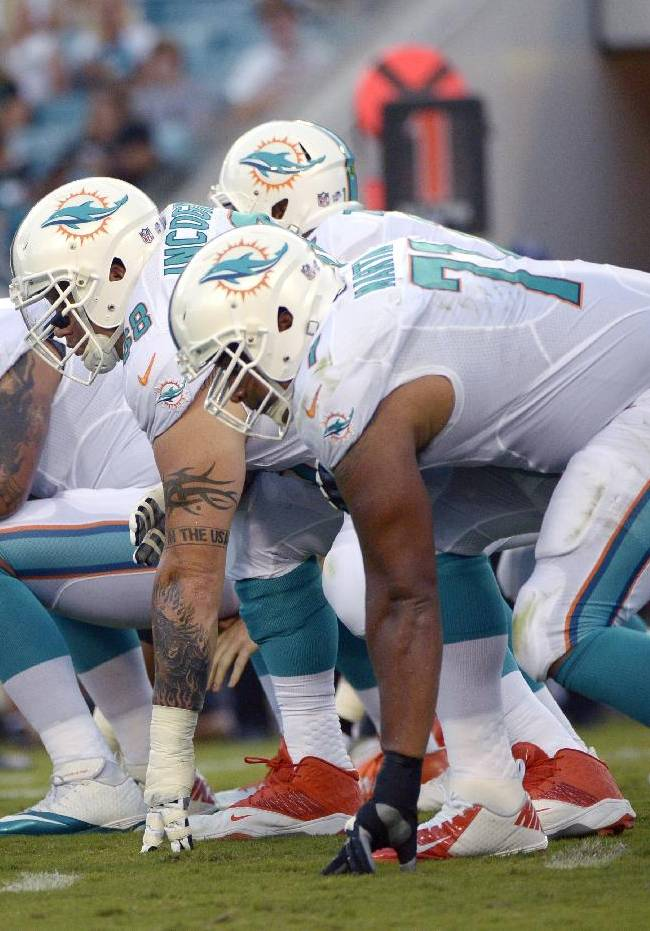 In this Aug. 9, 2013, file photo, Miami Dolphins center Mike Pouncey, left, guard Richie Incognito (68) and tackle Jonathan Martin (71) set up to block during the first half of an NFL preseason football game against the Jacksonville Jaguars in Jacksonville, Fla. Martin was subjected to