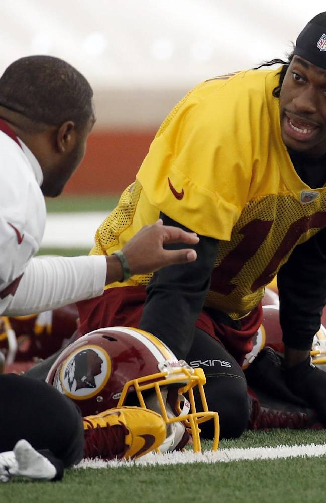 Washington Redskins quarterback Robert Griffin III, right, talks with fullback Darrel Young as they stretch during their NFL football practice Wednesday, Dec. 11, 2013, in Ashburn, Va. Kirk Cousins will start for the Redskins on Sunday, and Griffin III will be the No. 3 quarterback behind Rex Grossman
