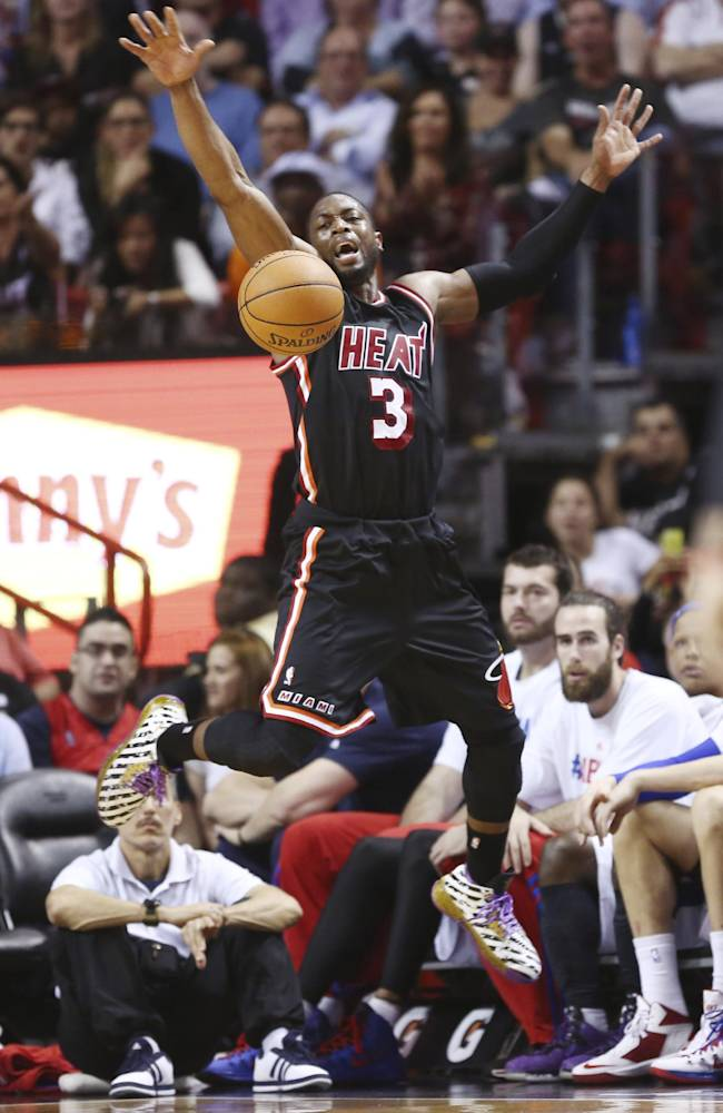 Miami Heat's Dwyane Wade (3) jumps in the air to keep a ball in bounds during the second half of an NBA basketball game against the Detroit Pistons in Miami, Monday, Feb. 3, 2014. The Heat won 102-96