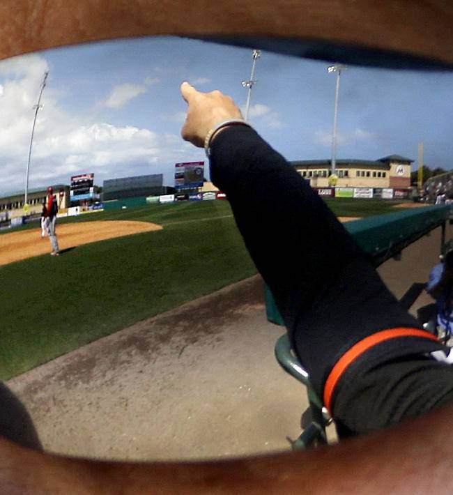 The arm of Miami Marlins third base coach Brett Butler is reflected in his sunglasses as he gestures to players on the field during the seventh inning of an exhibition spring training baseball game against the Washington Nationals, Saturday, March 15, 2014, in Jupiter, Fla