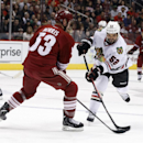 Chicago Blackhawks left wing Brandon Bollig (52) shoots on goal in front of Phoenix Coyotes defenseman Derek Morris (53) in the first period of an NHL hockey game on Saturday, Nov. 30, 2013, in Glendale, Ariz The Associated Press