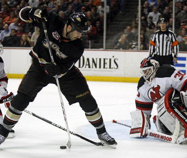 Anaheim Ducks left wing Dustin Penner, center, passes the puck behind him with New Jersey Devils defenseman Peter Harrold, left, and goalie Martin Brodeur, right, defending in the second period of an NHL hockey game Wednesday, Nov. 20, 2013, in Anaheim, Calif