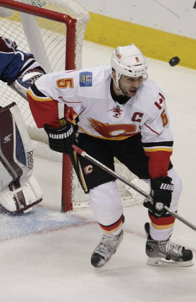 The puck bounces past Calgary Flames defenseman Mark Giordano (5) as Colorado Avalanche goalie Jean-Sebastien Giguere (35) defends the goal in the first period of an NHL game in Denver on Monday, Jan. 6, 2014
