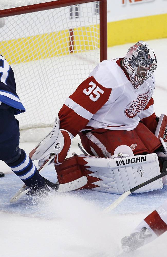 Winnipeg Jets' Bryan Little (18) scores on Detroit Red Wings' goaltender Jimmy Howard (35) and Jakub Kindl (4) during first period NHL action in Winnipeg on Monday, Nov. 4, 2013