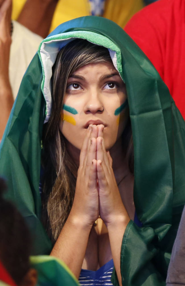 A Brazilian fan intensely watches the World Cup opening match between Brazil and Croatia at the Fan Fest complex in Recife, Brazil, Thursday, June 12, 2014. After taking the early lead in the opening match of the international soccer tournament, Croatia fell 3-1 to the five-time champion Brazil. (AP Photo/Dolores Ochoa)
