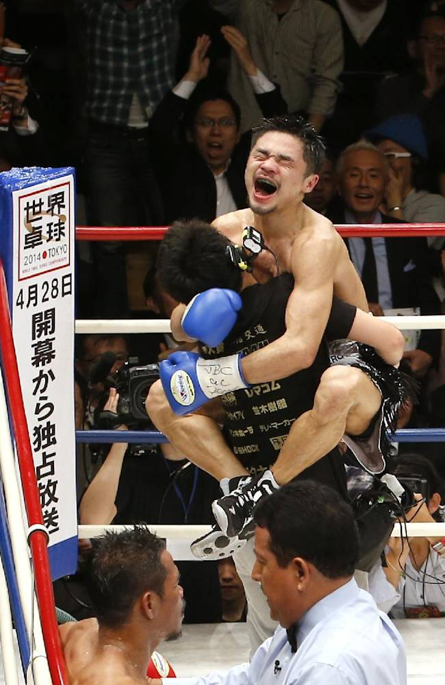 Japan's Kohei Kono celebrates with a member of his team after knocking out Thailand's Denkaosen Kaovichit, left bottom, in the eighth round of their boxing match for the vacant WBA World super flyweight title in Tokyo, Wednesday, March 26, 2014. Kono became the champion of the title