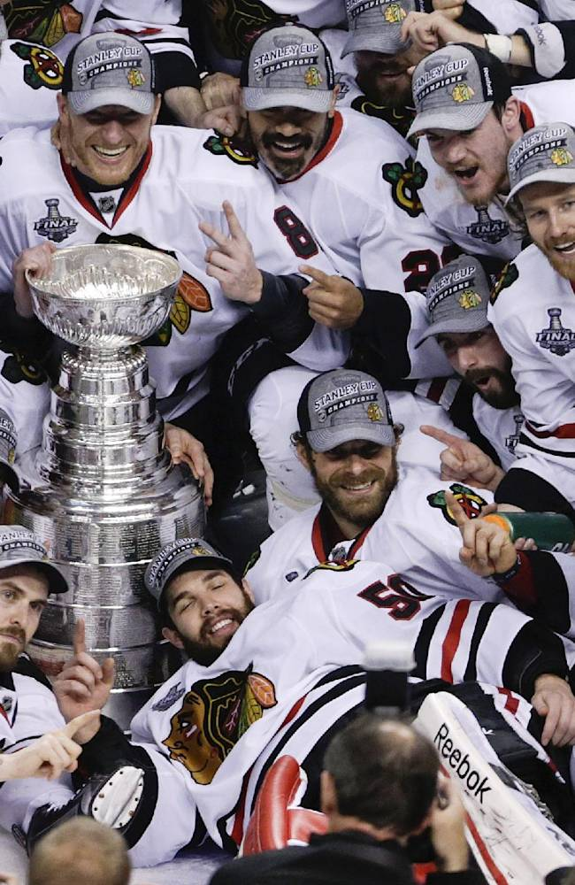 In this June 24, 2013 file photo, the Chicago Blackhawks pose with the Stanley Cup after beating the Boston Bruins 3-2 in Game 6 of the NHL hockey Stanley Cup Finals, in Boston. There are old faces in new places, new rules and a daunting challenge facing the Blackhawks, who attempt to become the first team to repeat as Stanley Cup champs in 15 years