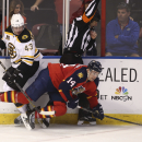 As Boston Briuns' Matt Bratkowski (43) and Florida Panthers' Tomas Fleischmann (14) chase the puck they skate into referee Steve Kozari during the third period of an NHL hockey game in Sunrise, Fla., Sunday, March 9, 2014. Boston won 5-2 The Associated P