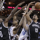 Brooklyn Nets' Jorge Gutierrez (13) and Andray Blatche (0) compete with Charlotte Bobcats' Cody Zeller (40) and Chris Douglas-Roberts (55) for a rebound during the first half of an NBA basketball game in Charlotte, N.C., Wednesday, March 26, 2014. (AP Photo/Chuck Burton)