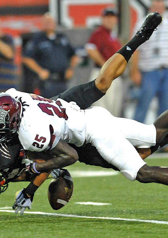 Arkansas State's J.D. McKissic, bottom, is tackled by Troy (Ala.) Chris Davis (25) during an NCAA college football game on Thursday, Sept. 12, 2013, in Jonesboro, Ark. Arkansas State defeated Troy 41-34
