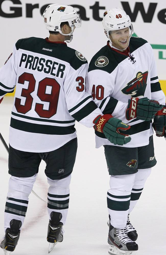 Minnesota Wild's Nate Prosser (39) and Steven Kampfer (40) celebrate an empty-net goal against the Winnipeg Jets during third-period preseason NHL hockey game action in Winnipeg, Manitoba, Thursday, Sept. 19, 2013