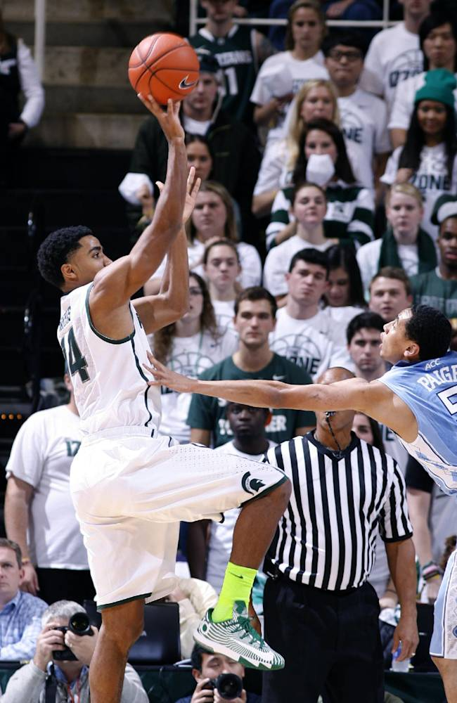 Michigan State's Gary Harris, left, shoots against North Carolina's Marcus Paige during the first half of an NCAA college basketball game, Wednesday, Dec. 4, 2013, in East Lansing, Mich. North Carolina won 79-65
