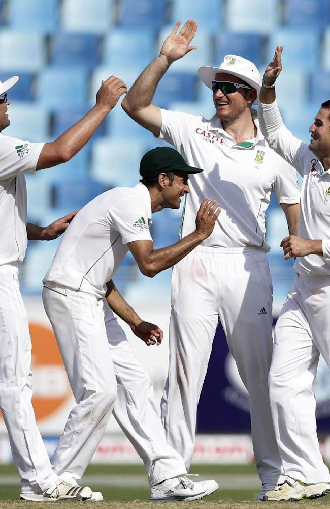South Africa's Dean Elgar, from right, celebrates with his teammates Graeme Smith, Imran Tahir and Jacques Kallis as taking the wicket of Pakistan's captain Misbah-ul-Haq during the fourth day of the second cricket test match of a two match series between Pakistan and South Africa at the Dubai International Cricket Stadium in Dubai, United Arab Emirates, Saturday, Oct. 26, 2013