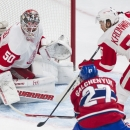 Detroit Red Wings goaltender Jonas Gustavsson makes a save against Montreal Canadiens' Alex Galchenyuk (27) as Red Wings' Niklas Kronwall defends during the first period of an NHL hockey game in Montreal, Saturday, April 5, 2014 The Associated Press