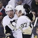 Pittsburgh Penguins' James Neal (18) celebrates his goal with teammate Sidney Crosby (87) in the first period of an NHL hockey game against the Boston Bruins in Boston, Saturday, Dec. 7, 2013. (AP Photo/Michael Dwyer)