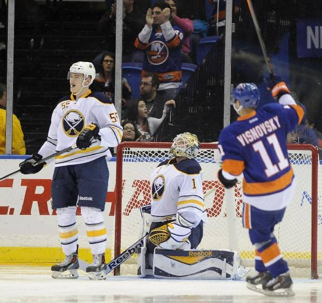 Buffalo Sabres' Rasmus Ristolainen and goalie Jhonas Enroth (1) react as New York Islanders' Lubomir Visnovsky (11) celebrates Ryan Strome's goal in the third    period of an NHL hockey game on Saturday, March 15, 2014, in Uniondale, N.Y. The Islanders won 4-1