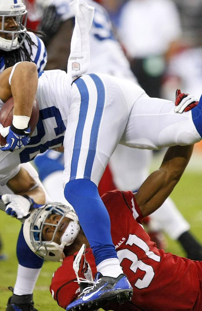 Indianapolis Colts' David Reed (85) is tackled by Arizona Cardinals cornerback Justin Bethel (31) during the first half of an NFL football game, Sunday, Nov. 24, 2013, in Glendale, Ariz