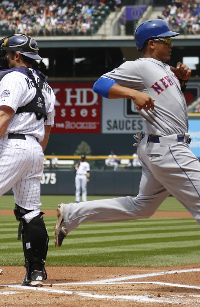 New York Mets' Juan Legares, front, scores on a single by Curtis Granderson as Colorado Rockies catcher Michael McKenry waits for the throw from the outfield in the first inning of a baseball game in Denver on Sunday, May 4, 2014