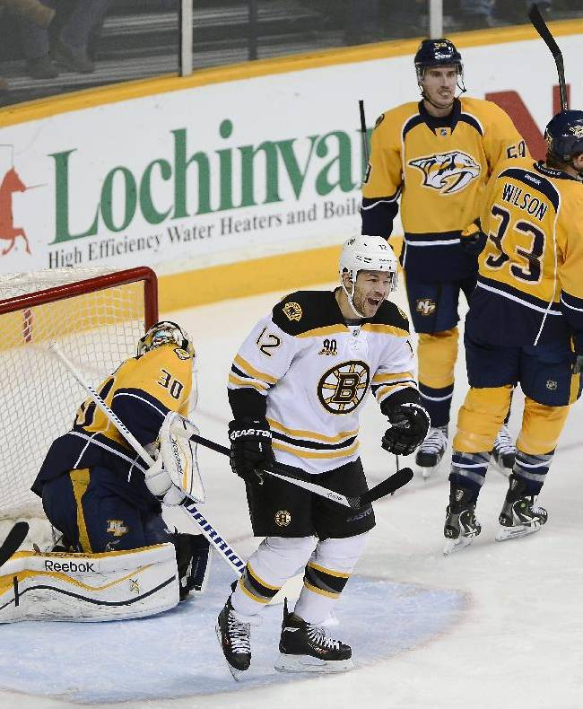 Boston Bruins right wing Jarome Iginla (12) celebrates after scoring a goal against Nashville Predators goalie Carter Hutton (30) in the first period of an NHL hockey game on Monday, Dec. 23, 2013, in Nashville, Tenn. Predators forward Colin Wilson (33) and defenseman Roman Josi (59), of Switzerland, skate away after the goal