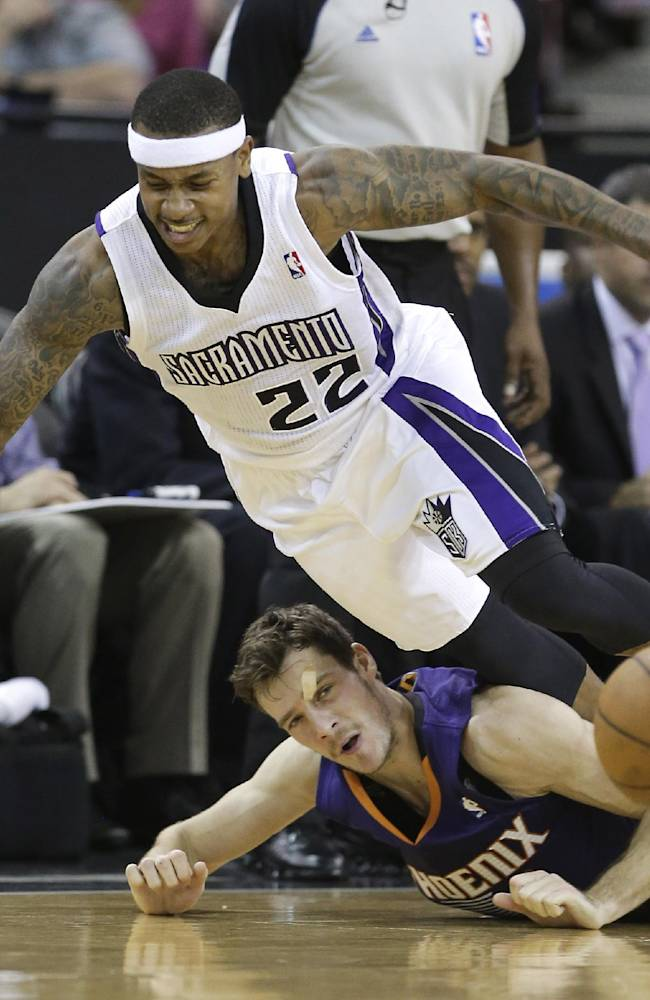 Sacramento Kings guard Isaiah Thomas, left, is tripped and fouled by Phoenix Suns Goran Dragic during the fourth quarter of an NBA basketball game in Sacramento, Calif., Tuesday, Nov. 19, 2013.  The Kings won 107-104