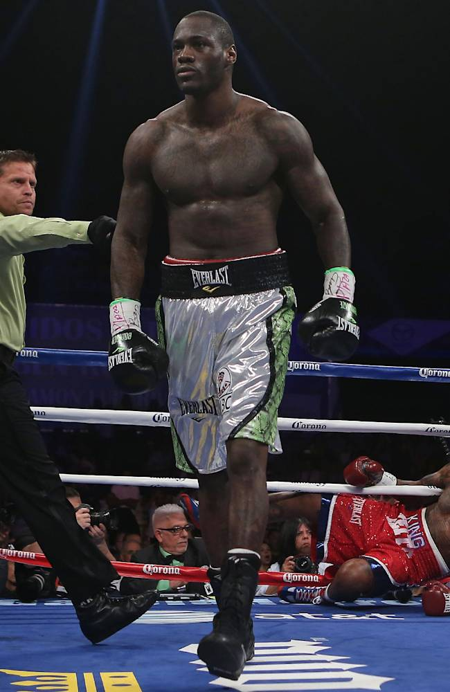 Referee Roberto Ramirez Jr., left, sends WBC Continental Americas Heavyweight Champion Deontay Wilder to a neutral corner while counting to Malik Scott during their heavyweight bout at the Ruben Rodriguez Coliseum in Bayamon, Puerto Rico, Saturday, March 15, 2014. Wilder defeated Scott by knock out in the first round