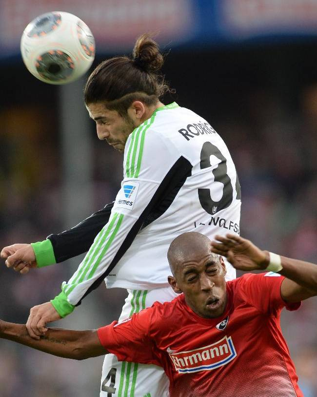 Wolfsburg's  Ricardo Rodriguez, left, challenges for the ball with Freiburg's  Gelson Fernandes during the German first division Bundesliga soccer match between SC Freiburg and VfL Wolfsburg in Freiburg, southern Germany, Sunday Dec. 8, 2013