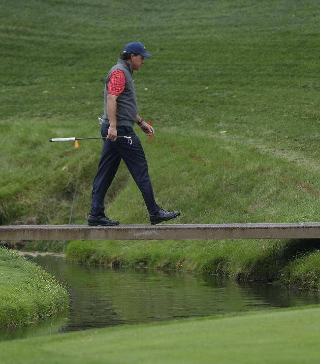 United States team player Phil Mickelson walks to the 14th green during a practice round for the Presidents Cup golf tournament at Muirfield Village Golf Club Wednesday, Oct. 2, 2013, in Dublin, Ohio