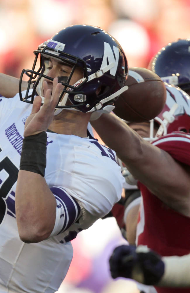 Wisconsin defensive end Pat Muldoon, right, forces a fumble on Northwestern quarterback Trevor Siemian during the second half of an NCAA college football game in Madison, Wis., Saturday, Oct. 12, 2013.  Siemian recovered his own fumble. Wisconsin upset Northwestern 35-6
