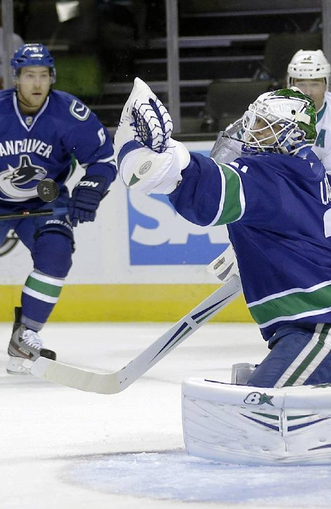 Vancouver Canucks goalie Eddie Lack, right deflects a shot on goal during the first period of a preseason NHL hockey game against the San Jose Sharks on Tuesday, Sept. 24, 2013, in San Jose, Calif