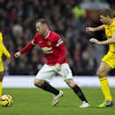 Manchester United's Wayne Rooney, centre, keeps the ball from Liverpool's Steven Gerrard during the English Premier League soccer match between Manchester United and Liverpool at Old Trafford Stadium, Manchester, England, Sunday Dec. 14, 2014