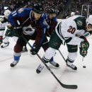 Colorado Avalanche defenseman Jamie McGinn, left, battles for control of the puck with Minnesota Wild defenseman Ryan Suter in the second period of a hockey game in Denver on Saturday, Oct. 11, 2014 The Associated Press