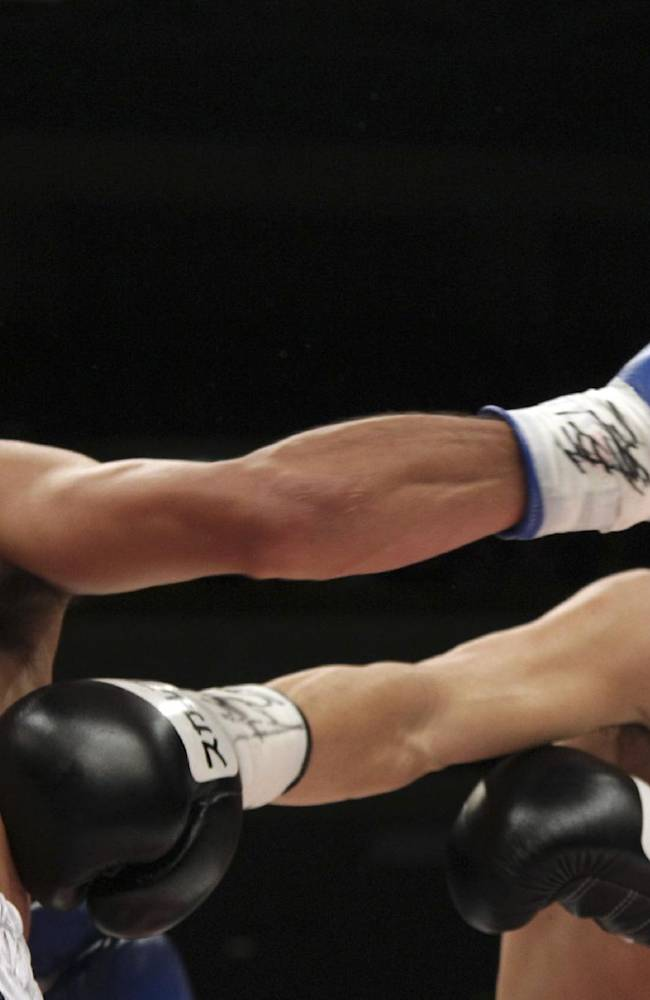 Japanese champion Shinsuke Yamanaka, right, and Mexican challenger Alberto Guevara exchange their punches in the second round of their WBC bantamweight title bout in Tokyo, Sunday, Nov. 10, 2013. Yamanaka knocked out Guevara in the ninth round to defend his title