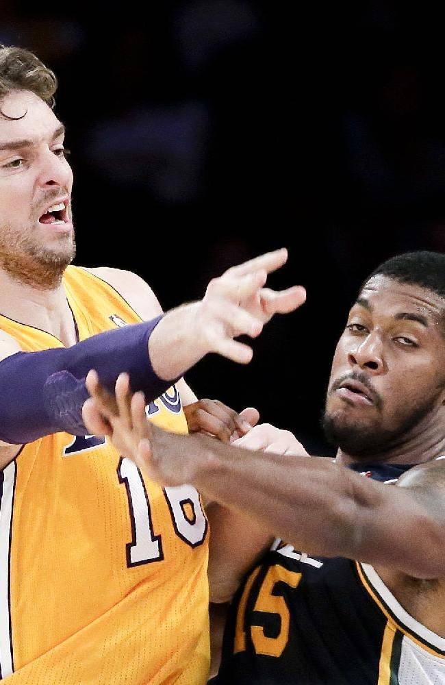 Los Angeles Lakers forward Pau Gasol passes around Utah Jazz forward Derrick Favors during the first half of a preseason NBA basketball game in Los Angeles, Tuesday, Oct. 22, 2013