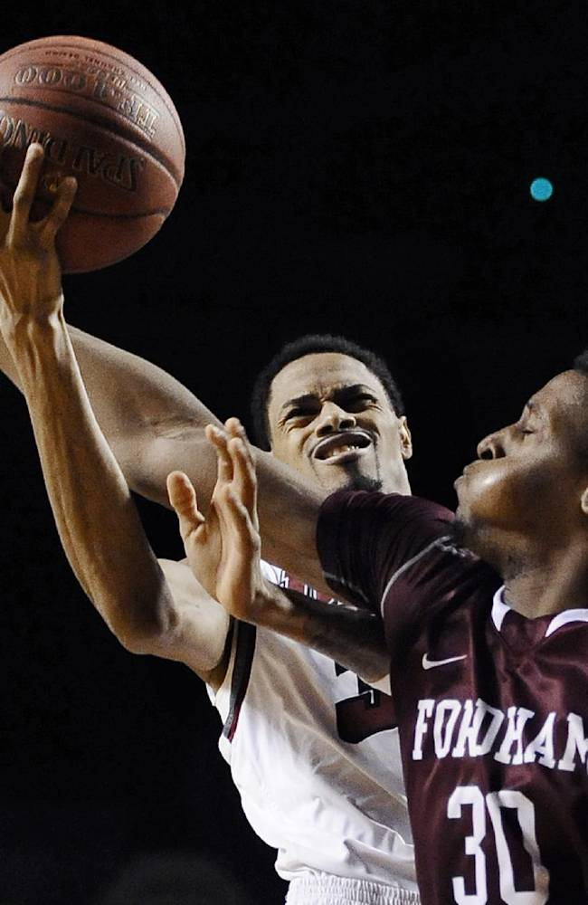 Fordham's Ryan Rhoomes, right, fouls Massachusetts' Raphiael Putney, left, during the second half of an NCAA college basketball game, Sunday, Jan. 26, 2014, in Amherst, Mass. Massachusetts won 90-52