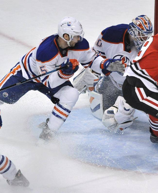 Chicago Blackhawks' Jonathan Toews (19), scores a goal against Edmonton Oilers goalie Devan Dubnyk while teammates Nick Schultz (15), and Ryan Nugent-Hopkins (83), look on during the second period of an NHL hockey game in Chicago, Sunday, Jan., 12, 2014. Chicago won 5-3